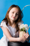 The girl with flowers. The girl in a white dress holds flowers in a pot Royalty Free Stock Photography