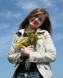 Girl with flowers. Pretty young girl with flowers on blue sky Stock Image