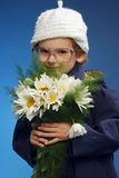 Girl with flowers. Little beautiful girl with flowers at blue background Stock Image