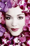 Girl in flowers. Black and white colored portrait of beautiful girl with stylish makeup and flowers around her face Royalty Free Stock Image