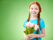 Girl with flowers. Adorable girl with bunch of tulips looking at camera Stock Photo
