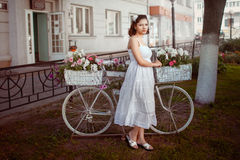 Girl with flowers. Beautiful girl with flowers baskets on cycle Royalty Free Stock Photo