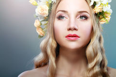 Girl With Flowers. Beautiful Girl With Flowers on Her Head.Beauty Model Woman Face. Perfect Skin. Professional Make-up.Makeup. Fashion Art Stock Photo