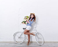 Girl with flowers and bicycle. Young attractive girl with flowers and bicycle. The girl in a hat, striped shirt and high heels Royalty Free Stock Images