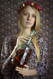 Girl in flowers with a bottle of wine Stock Images