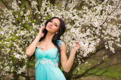 Girl in flowers of cherry Stock Image
