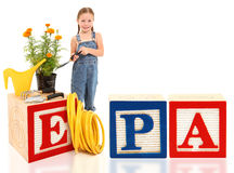 Girl with Flowers Environment EPA. Attractive 5 year old american girl with potted marigold plant and garden tools. Word EPA in large alphabet blocks royalty free stock images