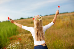 Girl with flowers on the field Stock Photos