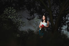 Girl with flowers in the forest. The girl in the dark forest, a lone rose in the hands Stock Photo