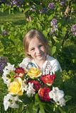 Girl with flowers in garden Stock Photos
