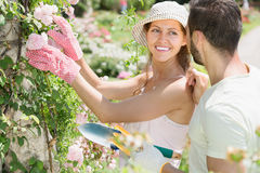 Girl in flowers garden with her boyfriend royalty free stock images