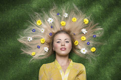 Girl with flowers in the hair. Pretty blonde girl lying on green meadow posing with some colourful flowers in her long blonde hair Royalty Free Stock Photo