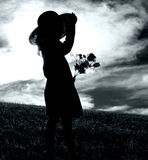 Girl with Flowers and Hat. Black and white portrait of young Girl with flowers and hat in a field with flowers royalty free stock image