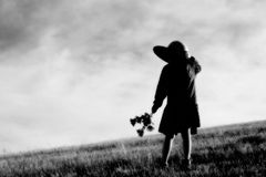 Girl with Flowers and Hat. Black and white portrait of young Girl with flowers and hat in a field with flowers stock photo