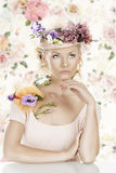 Girl with flowers on the hat looks up stock photography
