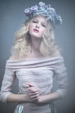 Girl with flowers on her head in a dress in the Russian style. Fog effect. Royalty Free Stock Images