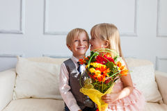 Girl with flowers is kissing boy. Stock Images