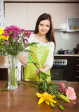 Girl with flowers on  kitchen table Stock Images