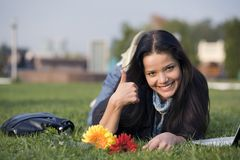 Girl with flowers and laptop on grass Stock Image