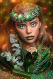 Girl with flowers. Magic golden girl with bright makeup. Streams of gold shiny drops on the background, cosmetics paint for body art. Big lips green shadows on Stock Photos