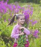 Girl with flowers in nature. Cheerful girl with flowers in nature Stock Photos