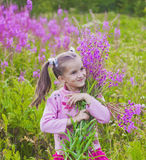Girl with flowers in nature. Cheerful girl with flowers in nature Stock Images