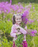 Girl with flowers in nature. Cheerful girl with flowers in nature Royalty Free Stock Images