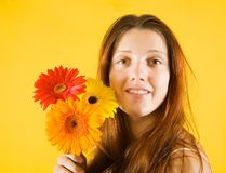 Girl with flowers over yellow Royalty Free Stock Photo