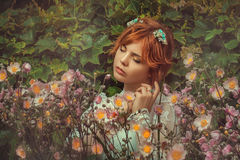 Girl in flowers. Portrait of a girl with red hair in colors royalty free stock photography