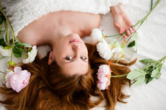 Girl with flowers on red hair lying in the bed Royalty Free Stock Image