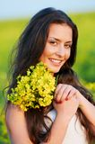 Girl with flowers at summer field Stock Image