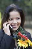 Girl with flowers talking by phone Stock Photo