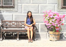 Girl with flowers. Young woman - indonesian girl with curly black hair sitting on wooden bench with pink flowers beside and renaissance painted wall behind royalty free stock images