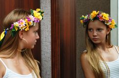 Girl with flowery crown. Young blond haired girl with flowery crown looking in mirror Stock Photography