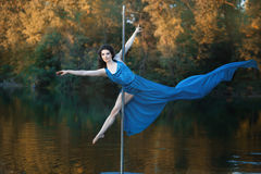 Girl in flowing dress is dancing around a pole dance. Stock Image