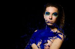 A girl with flowing hair and a beautiful blue make-up is bathed in blue paint. Stock Photography