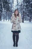 A girl with flowing hair in a beige fur coat and brown boots stands against the backdrop of the winter forest stock photography
