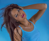 Girl with flowing hair on a blue background. Fashionable girl in the blue sleeveless vest with hair flying in the blue background Stock Photos