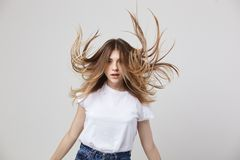 Girl with flowing hair dressed in a white t-shirt is on a white background in the studio stock photography