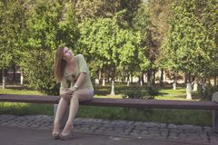 Girl with flowing hair in short shorts and shoes with heels sitting on a bench stock photos