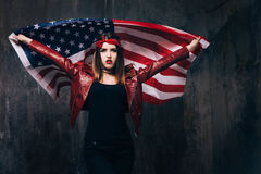 Girl with flying american flag behind the back. On dark background. Patriot, national event celebration, pride, usa citizen concept Stock Image