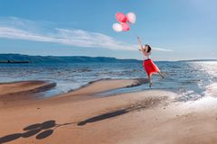 Girl flying on colored balloons stock images