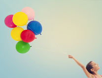 Girl flying colorful balloons in the blue sky Stock Photos