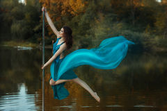 Girl flying dance, and her dress developing the wind. Royalty Free Stock Image