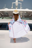 Girl in a flying dress on a yacht. Dress develops in the wind Stock Photo