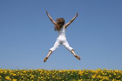 Girl flying in a funny jump. Girl in summer white clothes flying in a funny jump over flowering dandelion field Stock Photography