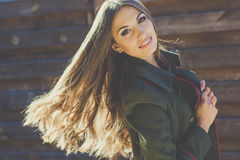 Girl with flying hair near wooden wall Royalty Free Stock Photo