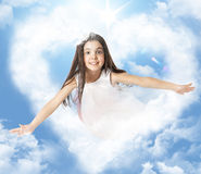 Girl flying through a heartshaped cloud Stock Photos