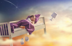Girl is flying in her bed. Kids dreams. Cute child girl is flying in her bed trough star sky royalty free stock images