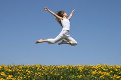 Girl flying in a jump. Girl in summer white clothes flying in a jump over flowering dandelion field royalty free stock photo